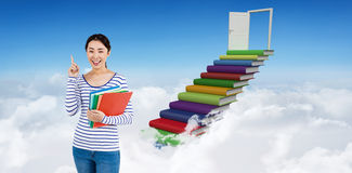 Composite image of cheerful woman pointing up while holding files Royalty Free Stock Images