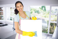 Composite image of cheerful woman wiping down white surface. Cheerful woman wiping down white surface against empty modern kitchen royalty free stock photography
