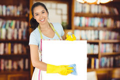 Composite image of cheerful woman wiping down white surface Royalty Free Stock Photo