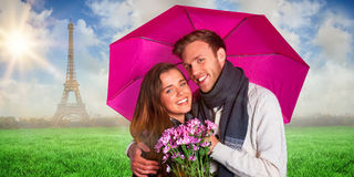 Composite image of cheerful young couple with flowers and umbrella Stock Image