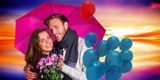 Composite image of cheerful young couple with flowers and umbrella Stock Images