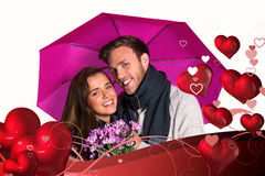 Composite image of cheerful young couple with flowers and umbrella. Cheerful young couple with flowers and umbrella against valentines heart design royalty free stock photo