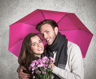 Composite image of cheerful young couple with flowers and umbrella Stock Photography