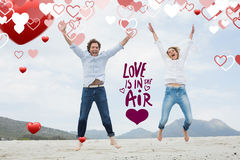 Composite image of cheerful young couple jumping at beach. Cheerful young couple jumping at beach against love is in the air stock image