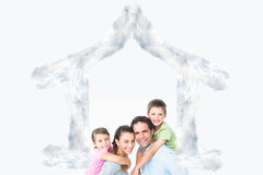 Composite image of cheerful young family looking at camera together Royalty Free Stock Image