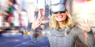 Composite image of cheerful young woman using reality virtual headset Stock Photo