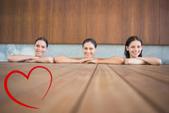 Composite image of cheerful young women in swimming pool Royalty Free Stock Image
