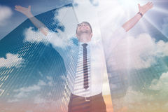 Composite image of cheering businessman with his arms raised up. Cheering businessman with his arms raised up against low angle view of skyscrapers at sunset Royalty Free Stock Photos