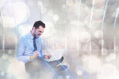 Composite image of cheering businessman sitting using his laptop Royalty Free Stock Image