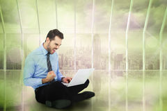 Composite image of cheering businessman sitting using his laptop Royalty Free Stock Images