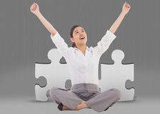 Composite image of cheering businesswoman sitting cross legged Royalty Free Stock Image
