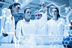 Composite image of chemistry students looking at a liquid Royalty Free Stock Image