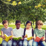 Composite image of children reading books at park stock photography