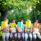 Composite image of children reading books at park stock image