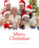 Composite image of children sitting with their family holding christmas boots Royalty Free Stock Photos