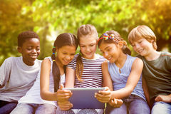 Composite image of children using digital tablet at park Stock Images