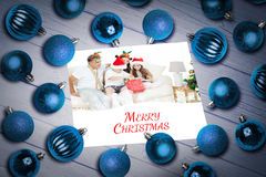 Composite image of christmas baubles on table Stock Images
