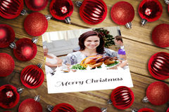 Composite image of christmas baubles on table Stock Photo