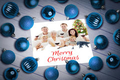 Composite image of christmas baubles on table Stock Image