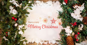 Composite image of christmas card. Christmas card against christmas decoration with fake snow on wooden plank Royalty Free Stock Images