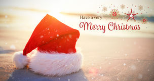 Composite image of christmas card. Christmas card against santa hat on the beach