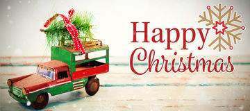 Composite image of christmas card. Christmas card against toy tempo carrying christmas fir on wooden plank Stock Photography