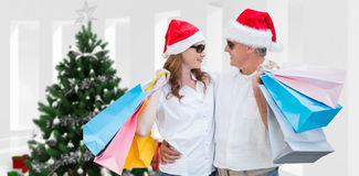 Composite image of christmas couple with shopping bags Royalty Free Stock Photos