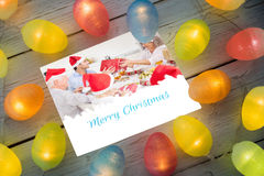 Composite image of christmas lights on table. Christmas lights on table against a happy family christmas card Stock Images