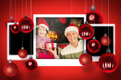 Composite image of christmas photographs. Christmas photographs against portrait of smiling father and son at christmas Royalty Free Stock Photos