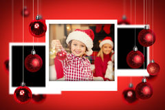 Composite image of christmas photographs. Christmas photographs against son wearing santa hat holding baubles in front of his family Royalty Free Stock Photo