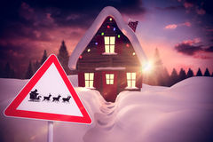 Composite image of christmas road sign. Christmas road sign against christmas house Royalty Free Stock Image