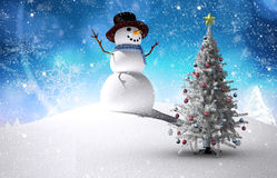 Composite image of christmas tree and snowman. Against snowy landscape with fir trees Royalty Free Stock Photo