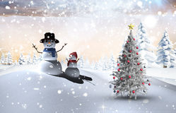 Composite image of christmas tree and snowman. Against snowy landscape with fir trees Stock Image