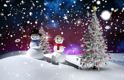 Composite image of christmas tree and snowmen Stock Photo