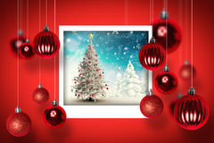 Composite image of christmas tree in snowy landscape. Christmas tree in snowy landscape against christmas photographs Stock Image