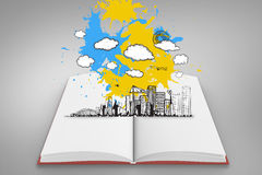 Composite image of cityscape graphic on paint splashes on open book Stock Photos