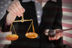 Composite image of close-up of american flag. Close-up of American flag against midsection of woman holding scales of justice and gavel Stock Photography