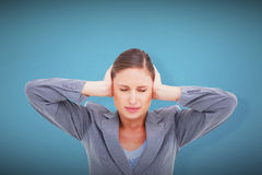 Composite image of close up of annoyed tradeswoman covering her ears Royalty Free Stock Images