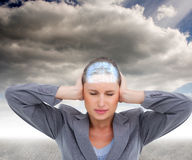 Composite image of close up of annoyed tradeswoman covering her ears Royalty Free Stock Photos