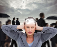 Composite image of close up of annoyed tradeswoman covering her ears Royalty Free Stock Image