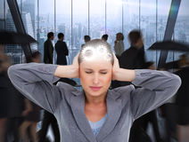 Composite image of close up of annoyed tradeswoman covering her ears Stock Photo