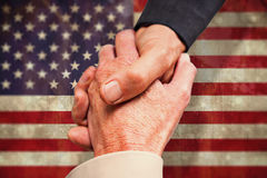 Composite image of close up on business people shaking hands Stock Images