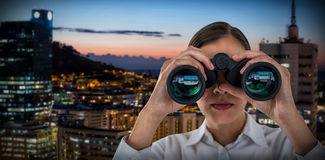 Composite image of close up of businesswoman looking through binoculars Stock Image