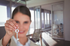 Composite image of close up of businesswoman showing new house key. Close up of businesswoman showing new house key against interior of modern office Stock Photography