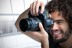 Composite image of close up of cheerful male photographer taking picture with camera. Close up of cheerful male photographer taking picture with camera  against Stock Photography