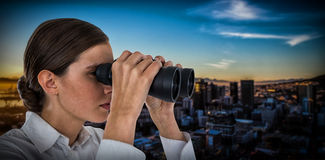 Composite image of close up of confident businesswoman looking through binoculars Stock Images