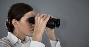 Composite image of close up of confident businesswoman looking through binoculars Stock Photos
