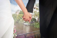 Composite image of close up of cute young newlyweds holding their hands Stock Images
