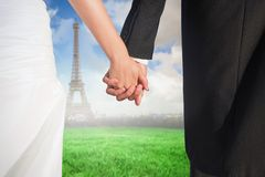 Composite image of close up of cute young newlyweds holding their hands Royalty Free Stock Photo