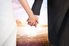 Composite image of close up of cute young newlyweds holding their hands Royalty Free Stock Images